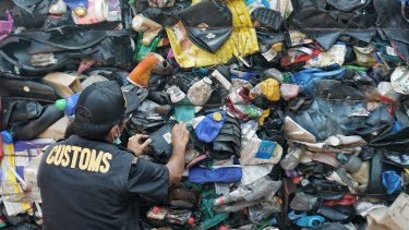 Indonesian customs official examines Australia's contaminated plastic waste at Batam port.