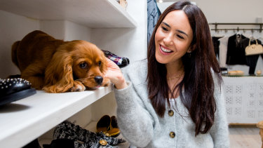 Jenna Isaacman with her 4-month-old cavoodle, Teddy, at her business 'Trading in Style' in Randwick.
