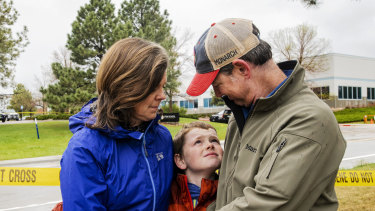 Kelly and Steve Holley hold their son Nate, 12, across the street from the STEM School Highlands Ranch in Highlands Ranch, Colorado.