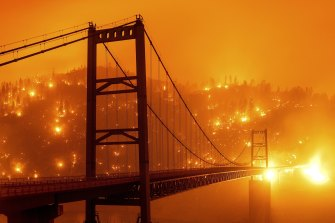 Embers light up a hillside behind the Bidwell Bar Bridge as the Bear Fire burns in Oroville, California during America's deadly 2020 fire season.