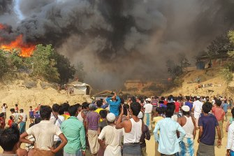 Rohingya refugees watch a fire destroy their camp in southern Bangladesh on Monday.