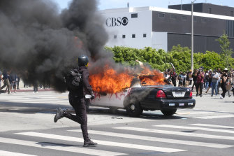 A police car burns during protests in Los Angeles over the death of George Floyd.