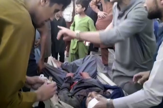People try to help a wounded man near the site of one of the bombings outside Kabul airport.