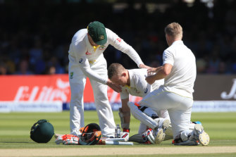 Chris Rogers (centre) steadies himself after copping a nasty blow at Lord's.