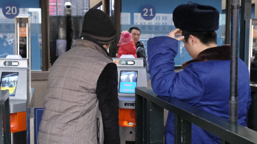 Train travellers are confronted by a new facial recognition system as they travel home from Beijing for Chinese New Year.