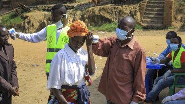 People crossing the border at Kasindi, on the border between Congo and Uganda,   have health checks.