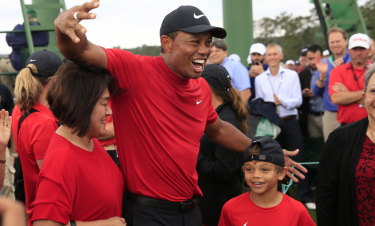 Family affair: Tiger Woods, in his  Sunday-best red and black,  with son Charlie.