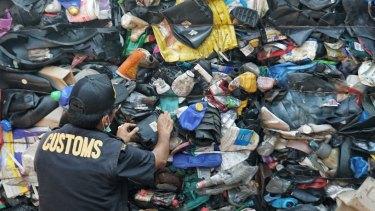 Indonesian customs official examines Australia's contaminated plastic waste at Batam port.