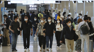 People wearing face masks arrive at the domestic flight terminal of Gimpo airport in Seoul.