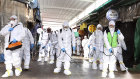 Workers wearing protective suits spray disinfectant as a precaution against the coronavirus at a market in Bupyeong, South Korea.