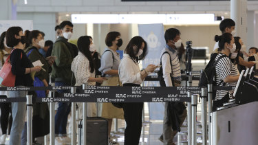 Passengers wearing face masks line up to board their planes at the domestic flight terminal of Gimpo airport in Seoul.