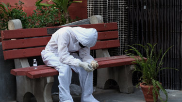 A relative of a Covid-19 fatality wears personal protective equipment (PPE) while sitting on a bench outside a cremation hall at the Nigambodh Ghat crematorium in New Delhi India, on Monday, April 19, 2021.