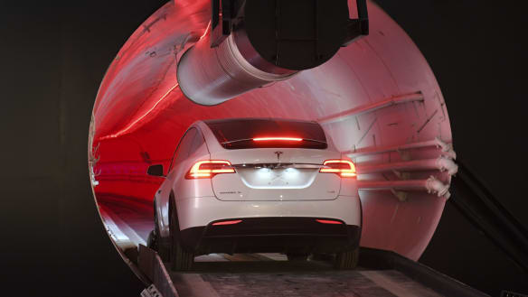 A modified Tesla Model X drives in the tunnel entrance before an unveiling event for the Boring Co.