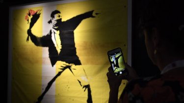 A viewer takes a photo of an art piece by Banksy in Sydney.