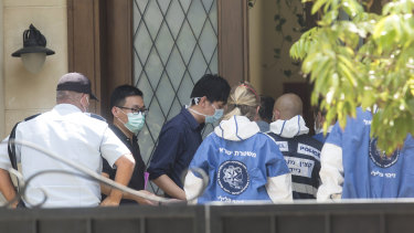 Israeli police workers enter the house of Du Wei after he was found dead in his home in Herzliya, Israel.
