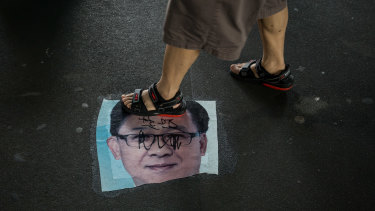 A demonstrator walks over a photo of Junius Kwan-yiu Ho, a Hong Kong legislator, during a protest in the Yuen Long district.