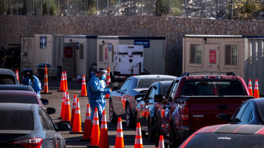 A medical worker wearing personal protective equipment (PPE) registers a person in a vehicle at a COVID-19 drive-thru testing site in El Paso, Texas.