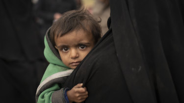 A woman holds her son as they wait to be screened by US-backed Syrian Democratic Forces (SDF) after being evacuated out of the last territory held by Islamic State militants, in the desert outside Baghouz, Syria, last week.