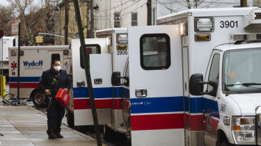 A paramedic wearing a protective mask walks past ambulances lined up outside Wyckoff Heights Medical Centre in Brooklyn.
