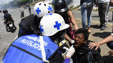 Medical personnel give first aid to a protester during a military uprising in Caracas on Tuesday.