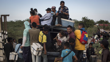 Vendors approach Venezuelan migrants as they ride in a pickup truck in the border town of Paraguachon, La Guajira, Colombia, in  August.