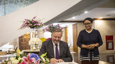 Anthony Albanese signs a guest book as Indonesian Foreign Minister Retno Marsudi looks on at the Indonesia foreign ministry office in Jakarta.