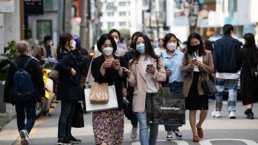 People wearing protective masks walk through the Garosu-gil neighborhood of the Gangnam district of Seoul, South Korea, on Saturday.