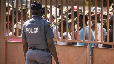 A police officer stands guard as residents queue to receive parcels of food aid in Finetown, south of Johannesburg.