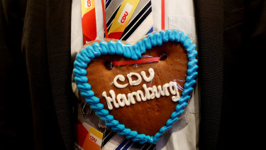 A party member wears a heart-shaped ginger bread cookie necklace during the Christian Democrat Union (CDU) party conference in Hamburg, Germany.