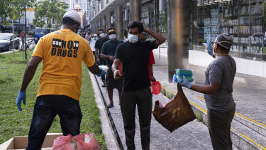 Volunteers distribute food and beverage for free to migrant workers in Little India in Singapore on Saturday.