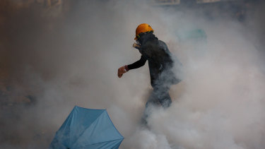 A protester walks in a cloud of tear gas during a protest against a proposed extradition law in Hong Kong.