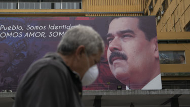 A pedestrian passes a billboard featuring an image of Venezuelan President Nicolas Maduro in Caracas.