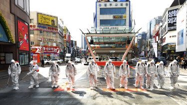 South Korean army soldiers wearing protective suits spray disinfectant to prevent the spread of the COVID-19 in Daegu.