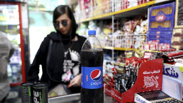 An Iranian customer buys a Pepsi in a grocery store in downtown Tehran.