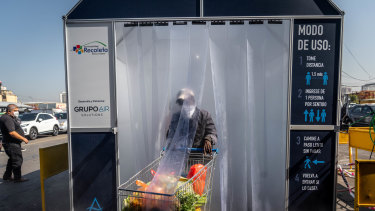 A person wearing a protective mask pushes a grocery cart through a decontamination chamber at the La Vega Central fruit and vegetable market in Santiago, Chile.