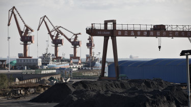 Piles of coal sit near port facilities as gantry cranes stand in the background at the Qinhuangdao Port.