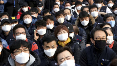Workers wearing masks to protect themselves from air pollution attend a rally against the government's labour policy in Seoul last week.