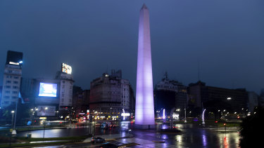 Cars drive past the illuminated Obelisk monument in Buenos Aires, Argentina, after power was restored.