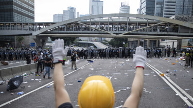 A protester raises his hands in front of riot police outside the Hong Kong Legislative Council on Wednesday.