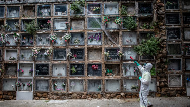 A worker wearing personal protective equipment waters the floral tributes of funeral urn niches in a columbarium at a cemetery in Spain on April 30.