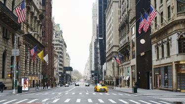 Taxis drive on a near-empty 5th Avenue, New York, on Friday.