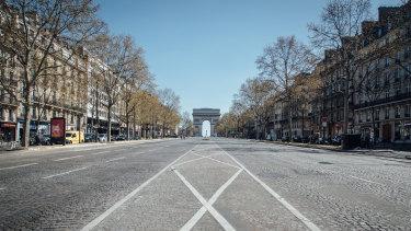 The Arc de Triomphe monument stands at the end of the empty Avenue de la Grande Armee in Paris, France.