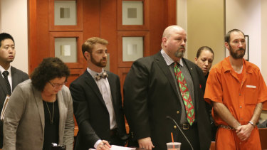 Johnny Bobbitt, in orange, stands during a hearing in New Jersey last year.