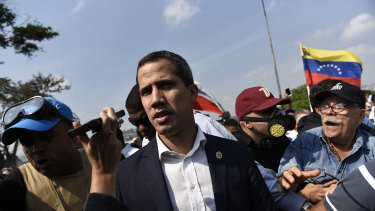 Juan Guaido, recognised by many Western nations as the interim president of Venezuela, centre, walks through a crowd after calling for people to rise against Maduro.