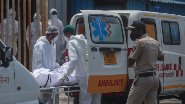 Health workers carry the body of a COVID-19 casualty outside a field hospital in Mumbai on May 4.