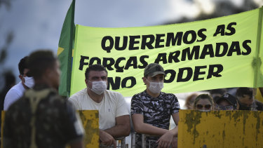 "Supporters of Brazilian President Jair Bolsonaro stand with a banner that reads in Portuguese, ""We want the armed forces in power,"" outside his residence last year."
