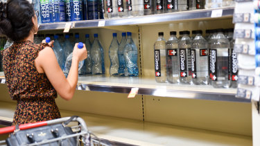 A customer stocks up on bottled water in Oakland Park, Florida, ahead of hurricane Dorian.