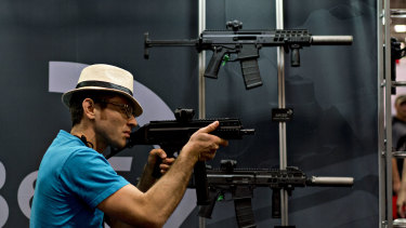 An attendee holds a rifle at the company's booth during the National Rifle Association (NRA) annual meeting in Dallas last year.