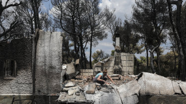 An owner searches through the debris of her house in Mati, Greece, on Wednesday.