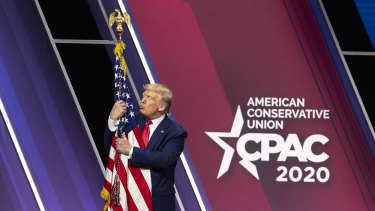 Then president Donald Trump hugs an American flag at the 2020 Conservative Political Action Conference.